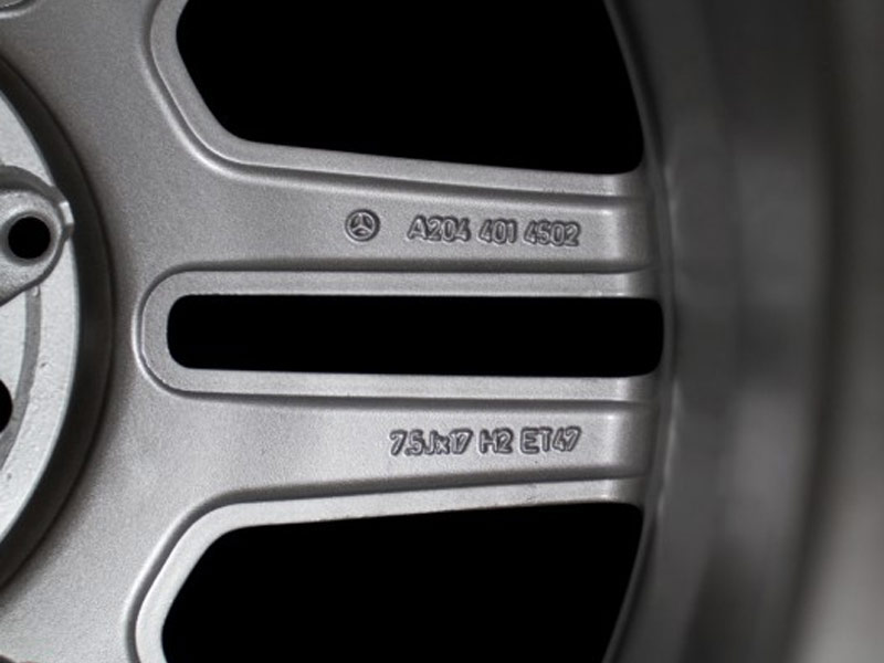 Image showing the reverse of a wheel with the Mercedes Benz logo, it's part number and specs.